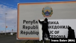 Changing the signs at Bogorodica on the North Macedonia-Greece border.