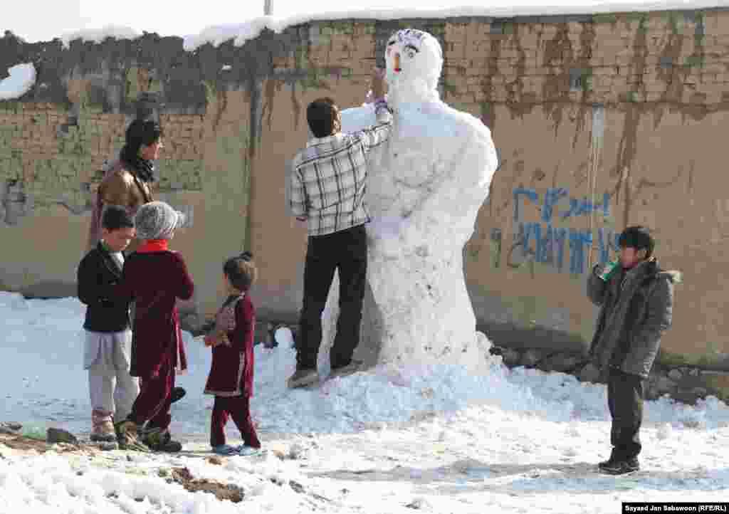 Афганистан. Взрослые с детьми лепят снеговика.