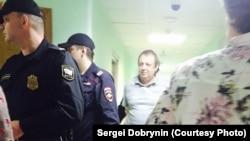 Сергея Калякина ведут в зал суда
