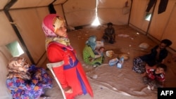 An Iraqi family who fled the city of Ramadi after it was seized by Islamic State militants, gathers inside their tent at a camp for the internally displaced in Amriyat al-Fallujah, 30 kilometers south of Fallujah, on May 22.