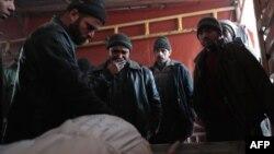 Adamlar Damaskyň etegindäki Douma şäherine howadan edilen hüjümiň netijesinde wepat bolan 18 ýaşly oglanyň jesediniň üstünde aglaýar, 28-nji dekabr, 2016.