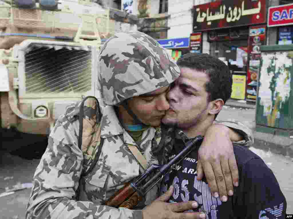 A civilian kisses an army soldier after troops took positions at major junctions in central Cairo on January 29.