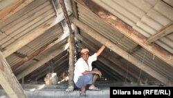 Жаксылык Айтореев показывает поведенные стропила на крыше своего дома.