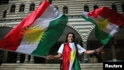 A woman waves Kurdish flags in Diyarbakir, Turkey, September 25, 2017. REUTERS