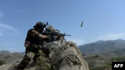 An Afghan security force personnel fires during an ongoing an operation against Islamic State (IS) militants in the Achin district of Nangarhar Province in April.
