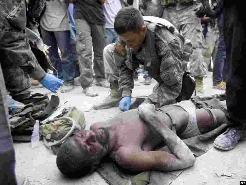 Амэрыканскія вайскоўцы аказваюць дапамогу чалавеку, які выжыў, правёўшы 12 дзён пад руінамі ў цэнтры сталіцы Гаіці, Порт-о-Прэнс, пасьля землятрусу.