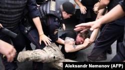 Orosz rendőrök őrizetbe vesznek egy tüntetőt, a rendőrség állítólagos túlkapásai ellett tartott moszkvai tüntetésen, 2019. június 12-én