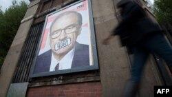 Un poster cu figura lui Rupert Murdoch afișat pe o stradă londoneză