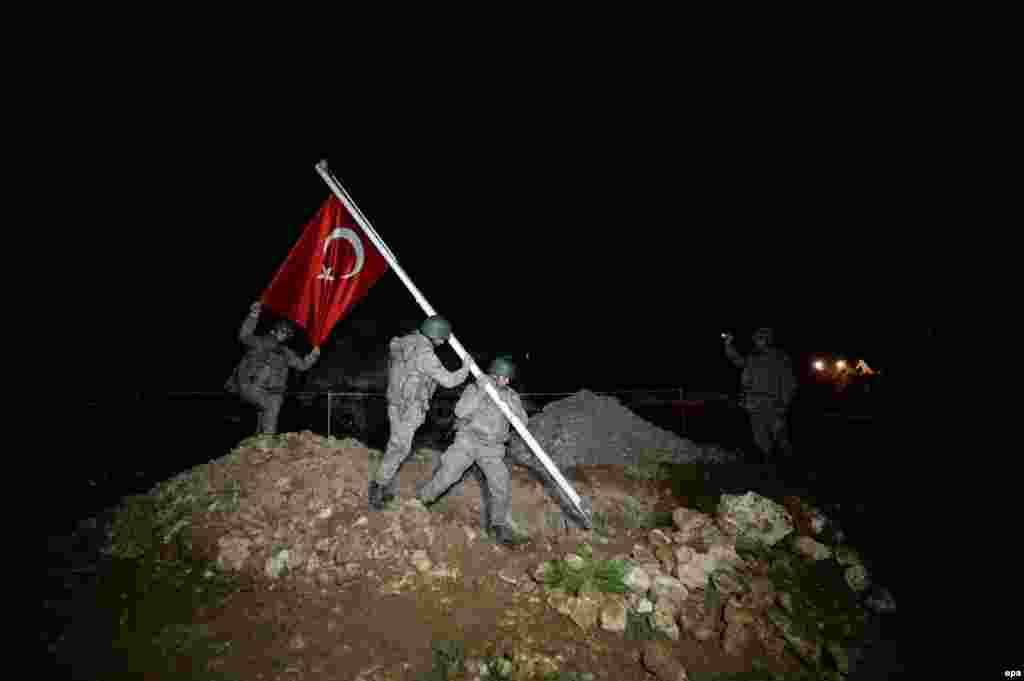 Turkish soldiers plant their national flag as they make their way to the tomb of Suleyman Shah for an evacuation operation near Aleppo on February 22. Shah's grave is a historic Ottoman tomb and dozens of Turkish troops who protect it have been evacuated from the embattled Syrian province. (epa/Okan Ozer)