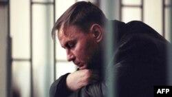Colonel Yury Budanov sits in the defendant's box during his murder trial in Rostov-na-Donu in April 2003.
