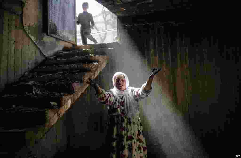A woman reacts while walking among the ruins of damaged buildings following heavy fighting between government troops and Kurdish fighters in the southeastern Kurdish town of Cizre in Turkey, near the border with Syria and Iraq on March 2. (AFP/Yasin Akgul)