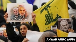 A supporter of the Shiite Hezbollah movement holds a poster of slain Iraqi paramilitary chief Abu Mahdi al-Muhandis (L) and Iranian Major General Qasem Soleimani (R) as the movement's leader delivers a speech on a screen, in the Lebanese capital Beirut. January 5, 2020