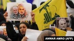 هواداران حزبالله تصاویری از قاسم سلیمانی و ابو مهدی مهندس را در دست دارند