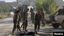 Afghan army soldiers stand over the body of a Taliban insurgent outside a prison in Ghazni on September 14.