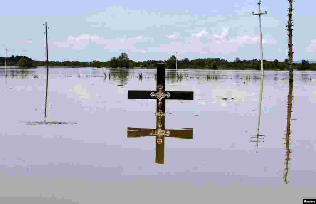A cross is seen in floodwaters at a cemetery in the village of Vojskova, Bosnia-Herzegovina, on May 19. (Reuters/Srdjan Zivulovic)