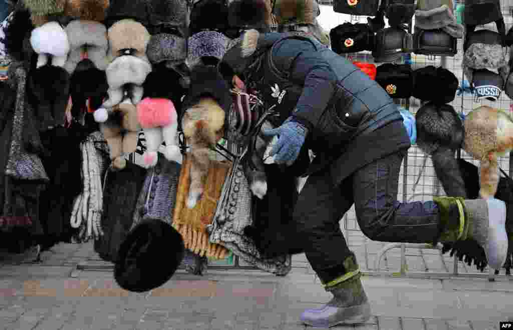 A street vendor tries to catch one of his winter hats, which was blown off a stand by strong winds on Red Square in Moscow.