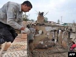 Ұлтаралық қақтығыс салдарынан қираған үйін қалпына келтіріп жатқан этникалық өзбек. Шарқ ауылы, Ош аймағы, Қырғызстан. 7 қазан 2010 ж.