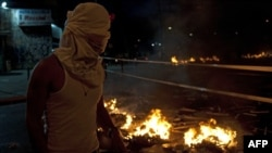 Учасник антиурядового протесту під час сутичок з поліцією. Каракас, 20 лютого 2014 року