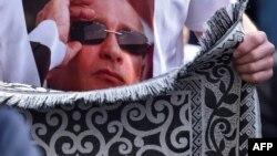 """Президент РФ В. Путин """"выглядывает"""" из-за мусульманского молитвенного коврика"""