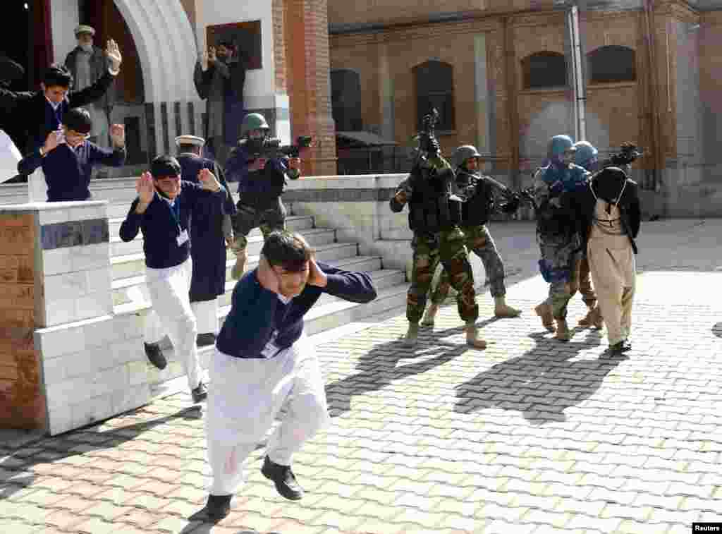 Schoolchildren flee as army soldiers conduct an exercise to repel a mock militant attack at Peshawar's Islamia Collegiate School on February 2.
