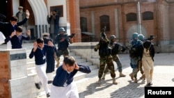 FILE: Schoolchildren flee as army soldiers conducting an exercise to repel militant attacks detain a mock-militant (R) at the Islamia Collegiate School in Peshawar.