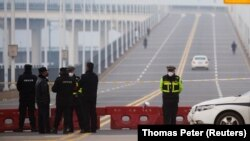 Police stand at a roadblock at a bridge crossing the Yangtze River to Hubei province in Jiujiang, Jiangxi province, China, as the country is hit by an outbreak of a new coronavirus, January 30, 2020
