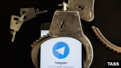 Кісенге салынған Telegram қосымшасы орнатылған смартфон (Көрнекі сурет).