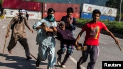 Supporters of Tahir-ul Qadri, Sufi cleric and leader of political party Pakistan Awami Tehreek (PAT), carry an injured fellow protester during the Revolution March in Islamabad on August 31, 2014.