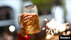 germany -- File photo of a beer being held aloft on the last day of the world's biggest beer festival, the 180th Oktoberfest, in Munich October 6, 2013. Beer sales rose in Germany, Europe's biggest producer, in the first half of the year thanks to a big j