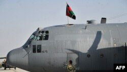 A member of the Afghan Air Force stands alongside a C-130 transport aircraft sporting the Afghan national flag at Kabul international airport. (file photo)