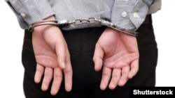 Generic – Isolated business man arrested with handcuffs on his back