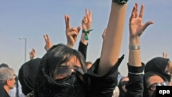 Iranian protesters shout slogans during an opposition rally at the cemetery