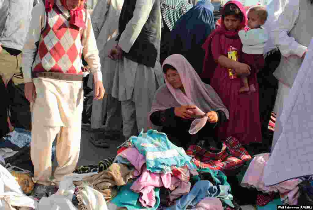 An Afghan woman sells used clothing in Kabul.
