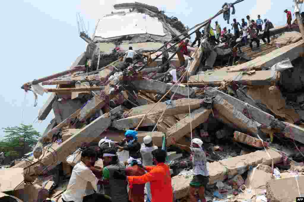 Bangladeshi volunteers and rescue workers are pictured at the scene after an eight-story building collapsed in Savar, on the outskirts of Dhaka. At least 190 people died in the disaster. (AFP/Munir uz Zaman)
