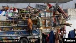 An Afghan refugee family stands by trucks loaded with their belongings as they wait to go back to Afghanistan in Peshawar in February.