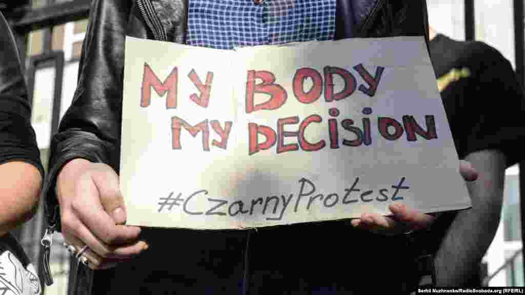 «Моє тіло – моє рішення»написано на плакаті, який тримає учасниця акції проти заборони абортів біля посольства Польщі в Києві. 3 жовтня 2016 року