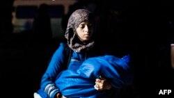 Женщина мигрант с младенцем в руках. Иллюстративное фото.