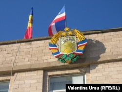 Герб и флаг (в центре) автономной республики Гагаузия. Слева - флаг Молдовы.