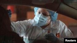 کارکن صحی حین اخذ نمونه از یک فرد برای آزمایش ویروس کرونا در امریکا