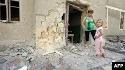Жінка і дитина біля зруйнованого будинку на Донбасі, 10 серпня 2015 року