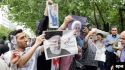 Iranian campaign activists distribute electoral posters of presidential candidates Rouhani and Raiesi after Friday prayers in Tehran, May 12, 2017