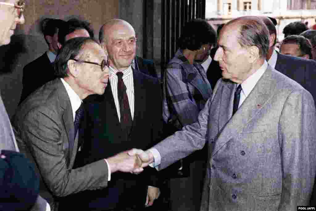 FRANCE - (FILES) In this file photo taken on March 29, 1989 French President François Mitterrand (R) shakes hands with Chinese American architect Ieoh Ming Pei, as Louvre Museum director Michel Laclotte looks on, during the public opening of the Louvre Py