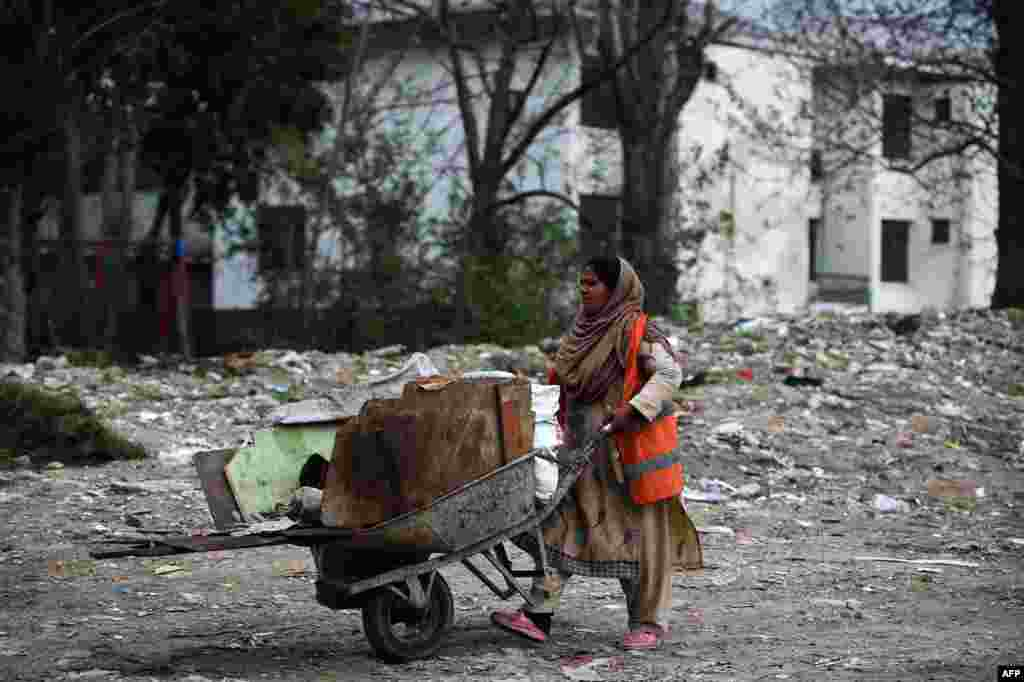 A Pakistani female worker pushes a trolley of material along a street in Islamabad. (AFP/Farooq Naeem)