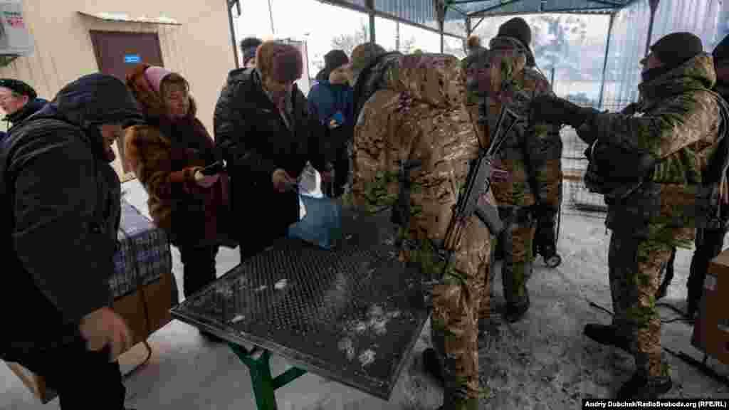 Ukrainian soldiers search belongings before people can begin the long march to separatist-held territory.