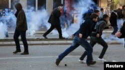 Protesters run away from tear gas fired by police officers during clashes at the Pristina on February 7.