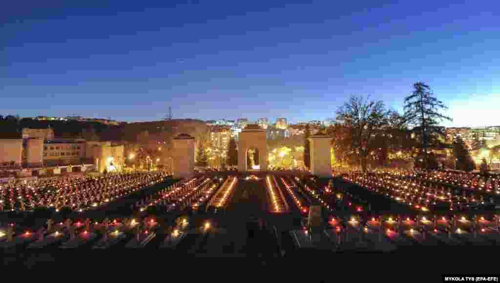 In Lviv, Ukraine, candles burn on Polish graves at Lychakiv cemetery.