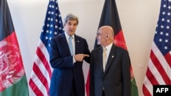 U.S. Secretary of State John Kerry (L) and Afghan President Ashraf Ghani pose for photographers during a Conference on Afghanistan in Brussels on October 4.