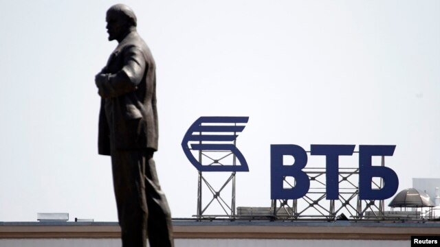 A sign for VTB Bank atop a building is seen beyond a monument of Soviet state founder Vladimir Lenin in central Stavropol, in southern Russia.