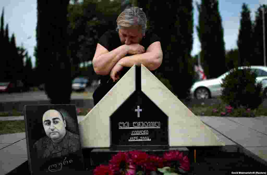 Dali Baramidze, 71, cries over the tombstone of her son Leri Lagurashvili on the 10th anniversary of the Georgian-Russian war at the memorial cemetery of the Georgian soldiers killed during the war in Tbilisi on August 8. (Reuters/David Mdzinarishvili)