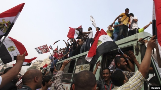 Supporters of the Muslim Brotherhood's presidential candidate, Muhammad Morsi, celebrate on top of a bus at Tahrir Square in Cairo on June 18.